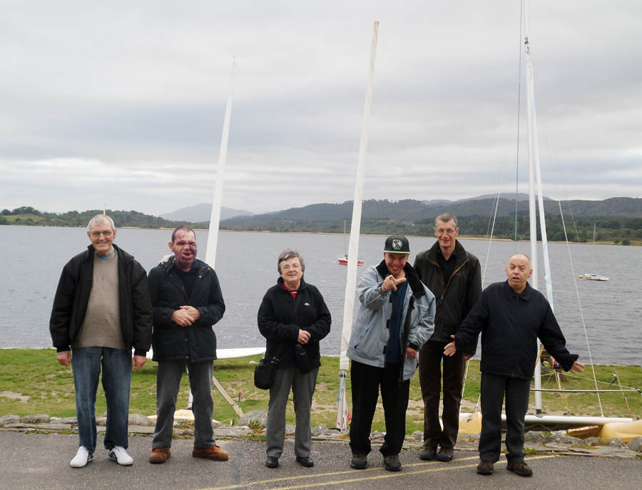 Service users beside a loch, getting ready to sail on a boat